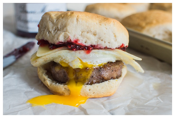 Sweet and Spicy Breakfast Sandwich with sausage, white cheddar, a fried egg, and raspberry preserves. Served on a buttermilk biscuit!